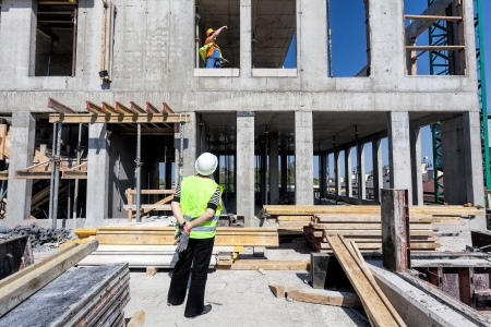 image of construction worker surveying a commercial construction site